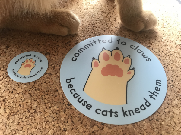 "Two sizes of sticker with the committed to claws logo, a paw in a high five position with the text ""committed to claws - because cats knead them"""