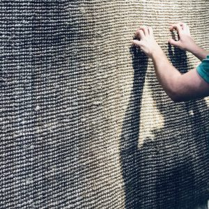 A man scratches on a sisal wall.