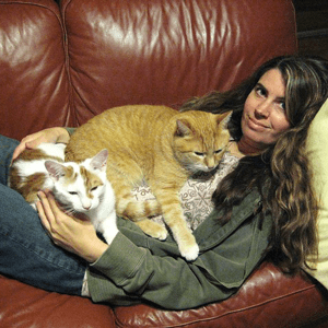 A woman is laying on a couch with two cats on top of her.