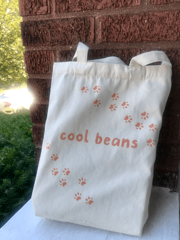 "Tote bag that says ""cool beans"" and has a trail of paw prints."