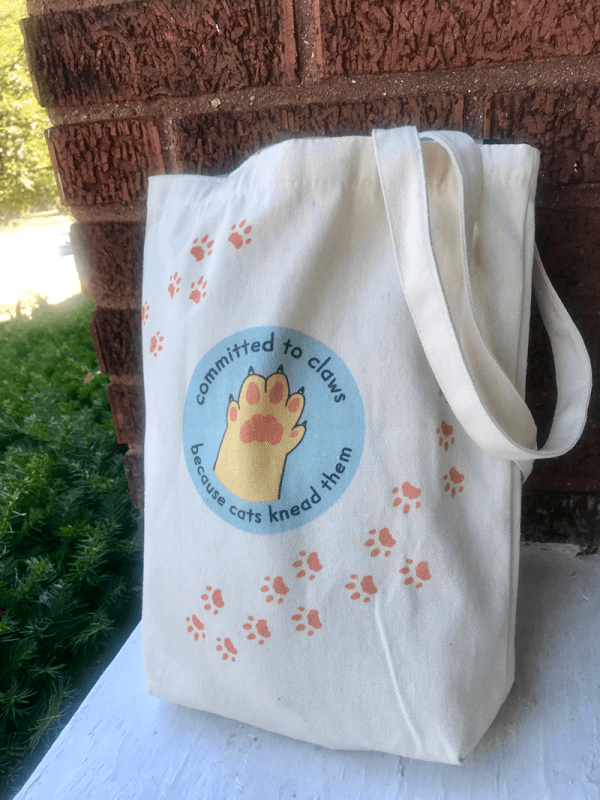 Tote back with the Committed to Claws paw logo and a trail of paw prints.