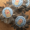 A round felt cat toy with feather trim around the edge. The felt has the committed to claws logo.