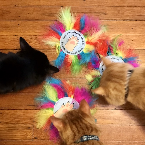 Three cats sniffing a pile of rainbow pride feather cat toys with the committed to claws logo.